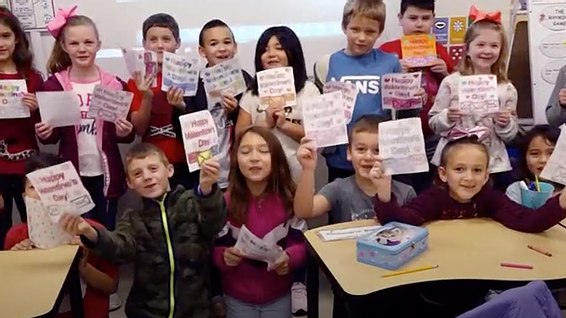 A Boerne Texas classroom of children proudly display their card art meant for foster kids