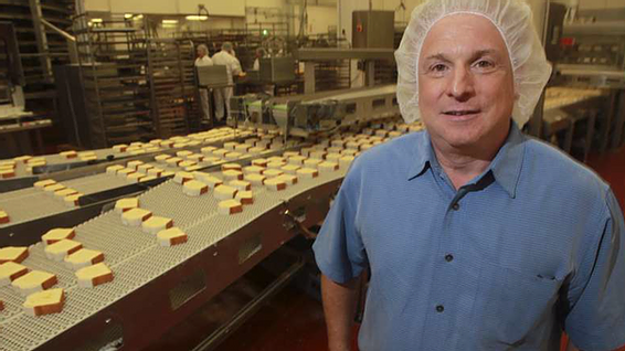 THRU Project Co-Founder Steve O'Donnell pictured in hairnet in front of his bakery manufacturing assembly line