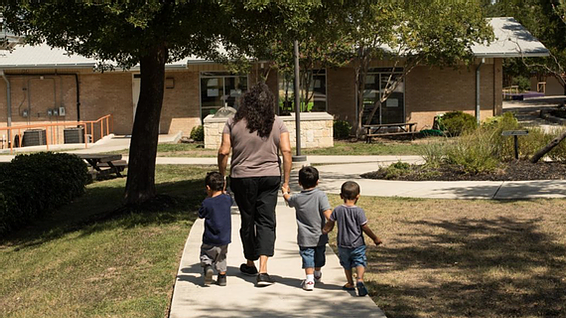 Mother walking down a sidewalk with her three small children