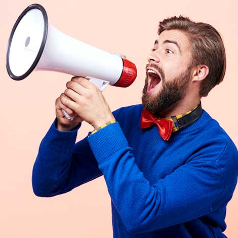 Bearded man shouting enthusiastically into megaphone