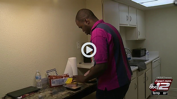 Former foster youth makes a sandwich in his kitchen