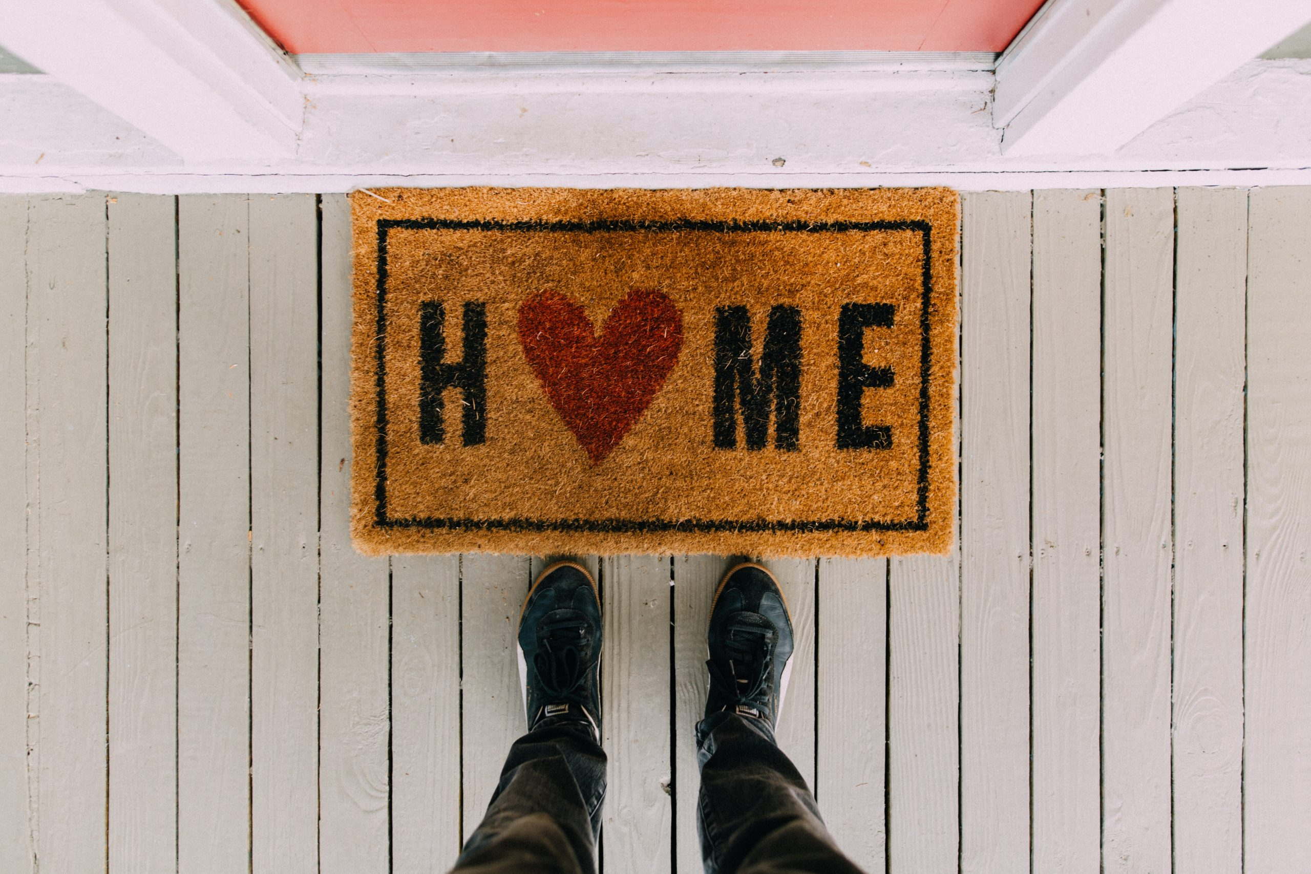 """Feet at welcome mat that says """"Home"""" with a heart"""
