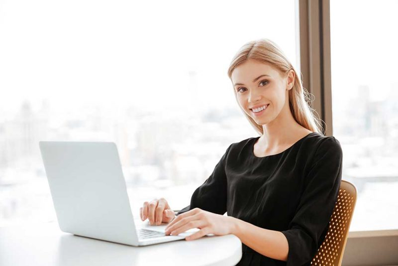 image of happy young woman worker sitting in office while using laptop computer and typing by keyboard look at camera
