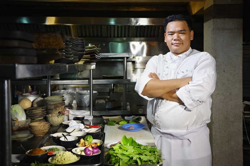 portrait of adult man at work as chef in the kitchen of an asian restaurant posing with arms crossed